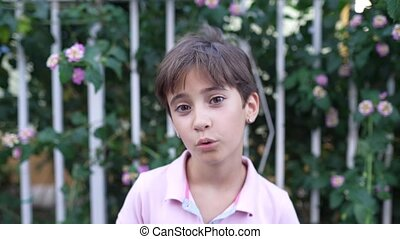 Eight years old girl smiling and blowing a kiss outdoors. ...