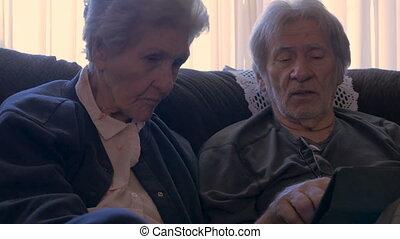 ein, älterer mann, erklärt, zu, ein, ältere frau, details, über, gebrauchend, a, tablette, in, 4k