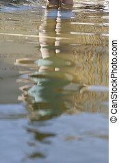Ein Maedchen spiegelt sich im Teich