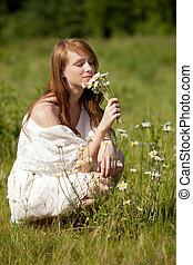 Eine junge, hübsche Frau pflückt Margeriten und andere...
