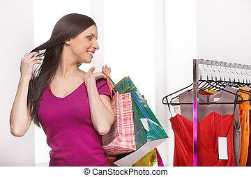 einzelhandel, store., heiter, junge frau, mit, einkaufstüten, anschauen, der, kleidet, in, einzelhandelsgeschäft