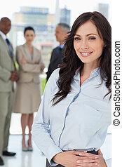 ejecutivo joven, mujer estar de pie, vertical, con, ella, manos, cruzado, en, ella, cadera