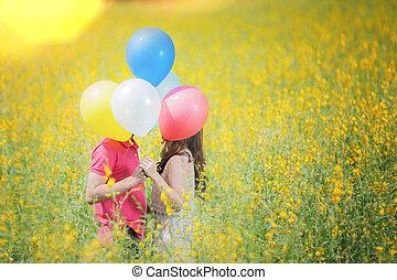 el besarse de los pares, en el jardín, flores amarillas
