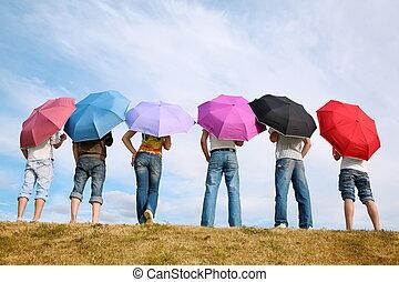 el, grupo de las personas, estantes, con, el, paraguas, en, a, pradera, por, el, espalda