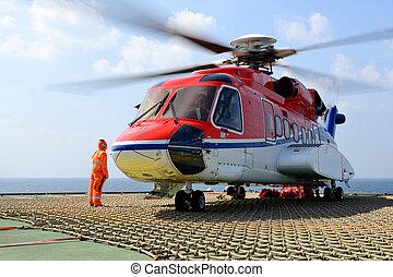 el, helicóptero, aterrizaje, oficial, cuidado de la toma, equipaje carga, a, helicóptero, en, plataforma petrolera, plataforma