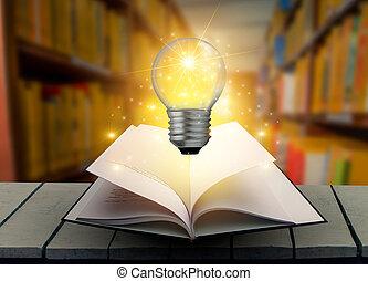 el, libro, foco, es, en, el, mesa., madera, en, el, libro de la biblioteca, y, foco, viejo, andrajoso, libro, en, un, tabla de madera, lectura, por, candlelight, vendimia, composición