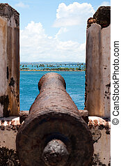 El Morro Fort Canon covered in rust points out towards the ocean.