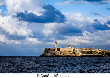 El Morro spanish fortress walls with lighthouse with sea in the foreground and clouds above, Havana, Cuba