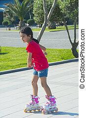 el, niña, paseos, en, pcteres de ruedas, en el parque