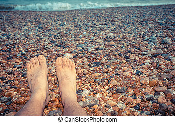 el, pies, de, un, joven, sentado on the beach