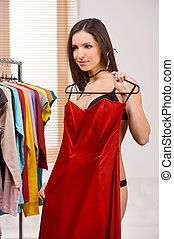 ela, gostar, este, dress., bonito, mulher jovem, em, langerie, segurando, vestido vermelho, e, olhando