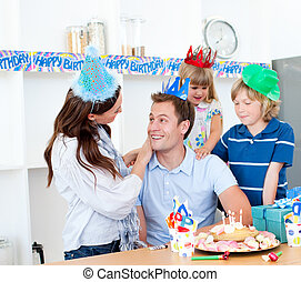 Elated man celebrating his birthday with his wife and his children in the kitchen