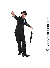 elated man in suit dancing with umbrella