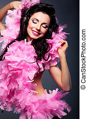 Elated positive woman in pink dress listening to the music
