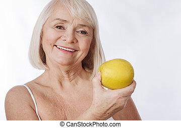 Elated senior woman having an apple in her hand