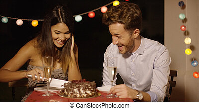 Elated young couple joking as they cut the cake - Elated ...