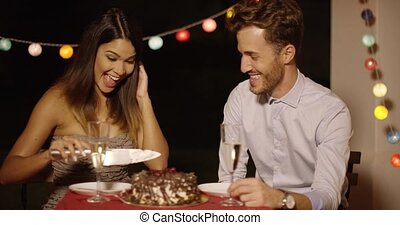 Elated young couple joking as they cut the cake - Elated...