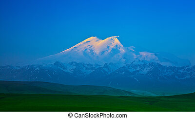 Elbrus mountain lit by the rays of the rising sun in the...