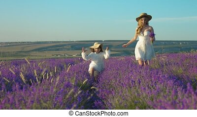 Elder and younger sisters in dresses running on a blossoming lavender field