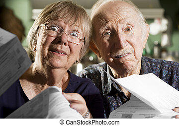 Elder Couple with Bills - Elder Couple at Home with Bills