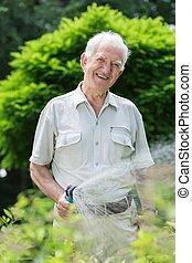 Elder gardener with hosepipe