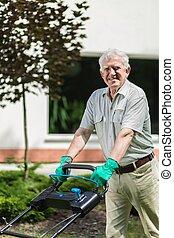 Elder gardener with lawn mower