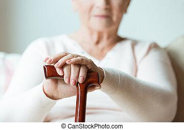 Elder holds hands on walking stick