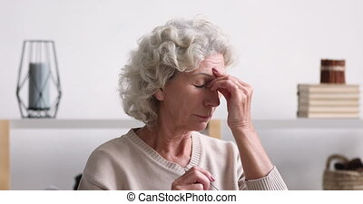 Elder 70s lady rubbing tired dry eyes feeling eye strain and fatigue concept. Upset senior woman holding glasses suffering from bad vision, headache. Old person having sight problem. Eyestrain concept