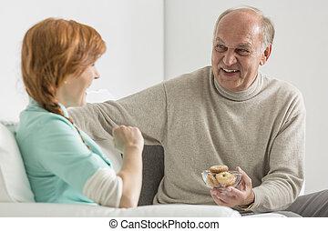 Elder man holding cookies