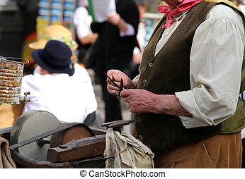 Elder man while sharpens knife in grindstone - Seniro while...