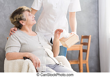 Elder pensioner with assisted living - Nurse giving a box of...