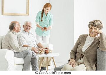 Elder people drinking coffee and eating cookies during...