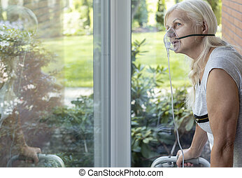 Elder person with an oxygen breathing mask looking at a window