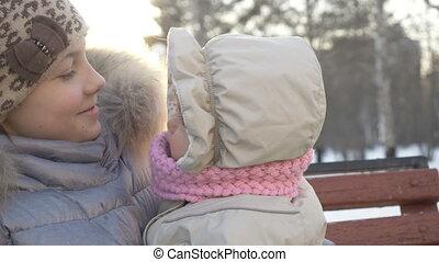 Elder sister holds her little baby in winter. - Elder sister...