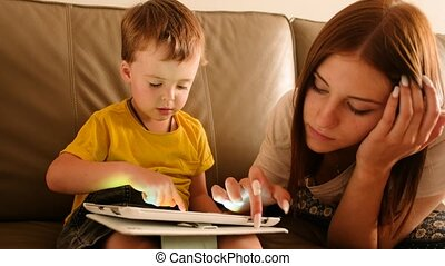 Elder sister playing with boy game on tablet at home