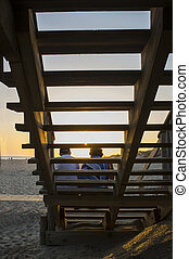 Elder tourist couple enjoying the magnificent sunrise of Islantilla, Huelva, Spain