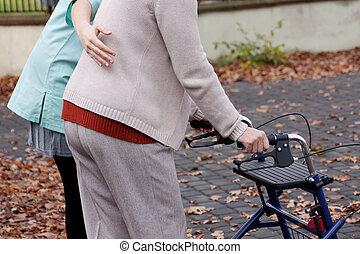 Elder with disability - Nurse helping elder person to walk...