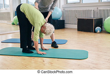 Elder woman exercising with help from trainer