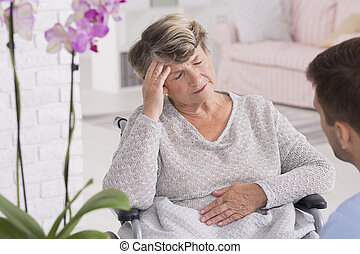 Elder woman on a wheelchair with headache - Shot of elder...