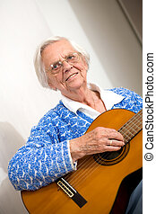 Elder woman playing guitar.