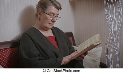 Elder woman reading a book at home