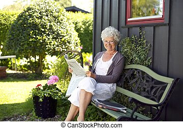 Relaxed elder woman sitting on a bench in backyard garden reading a newspaper looking at camera and smiling