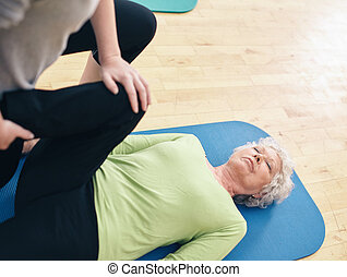 Elder woman receiving physical training from her personal...