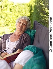 Senor woman sitting on lounge chair with a book and talking a nap. Senior lady sleeping in backyard with a novel