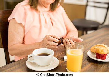 Elder woman taking pills before breakfast