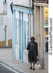 Elder woman with long coat  on the streets of Beja