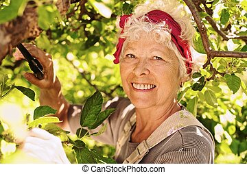 Elder woman working in her farm smiling