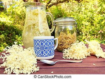 Elderberry blossom, jug with lemonade, tea of herbal cup, tea spoon on wooden table in nature.