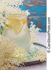 Home made refreshing elderflower lemonade on a wooden table. Macro, selective focus, vintage toned image