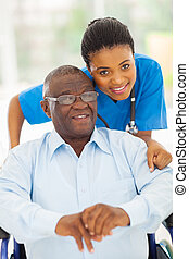 elderly african american man and caring young caregiver at...